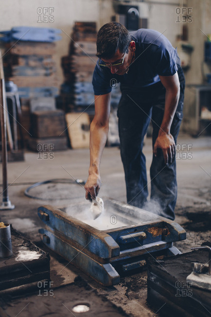 Foundry worker preparing his molds with parting powder