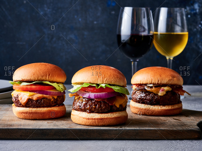 Three cheeseburgers and wine