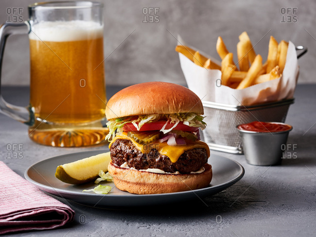 A cheeseburger with fries and beer