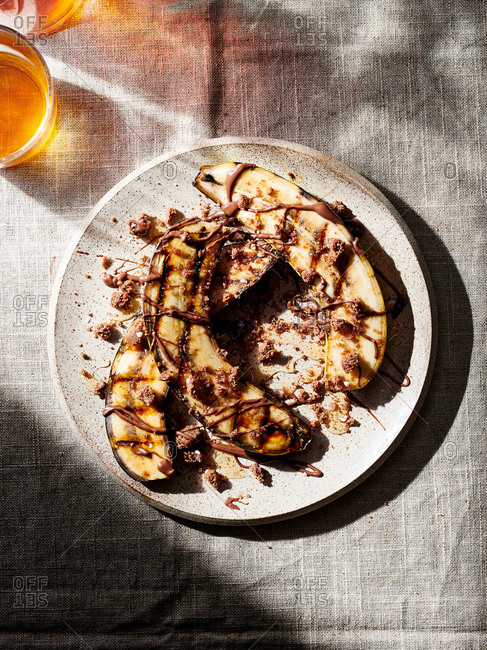 A plate of grilled bananas with chocolate peanut butter and crumbled cookies