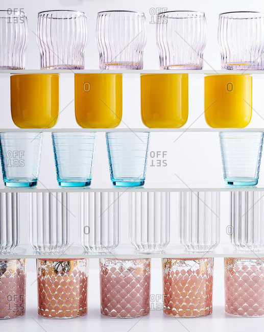 Colorful glasses on glass shelves