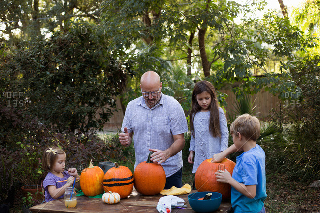 Family decorating and carving pumpkins together
