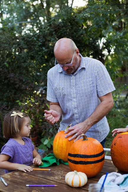Father and daughter carving a pumpkin together
