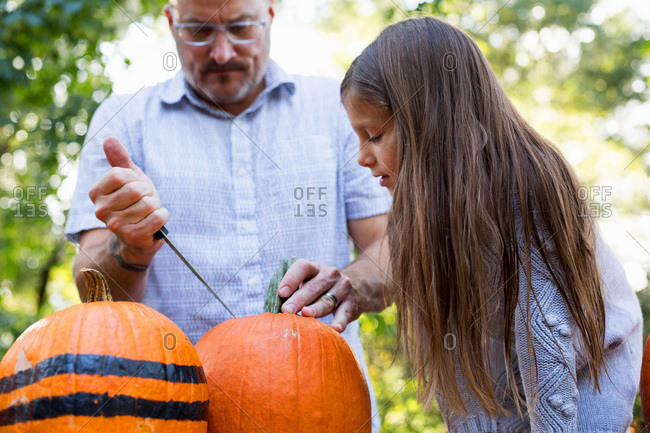 Girl watching her father carve a pumpkin