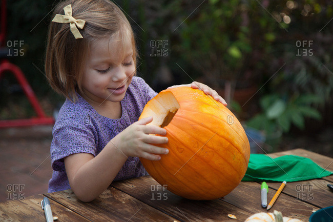 Smiling girl looking at the inside of a carved pumpkin