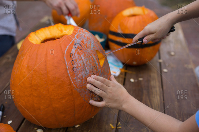 Close-up of a child carving a jack-o'-lantern