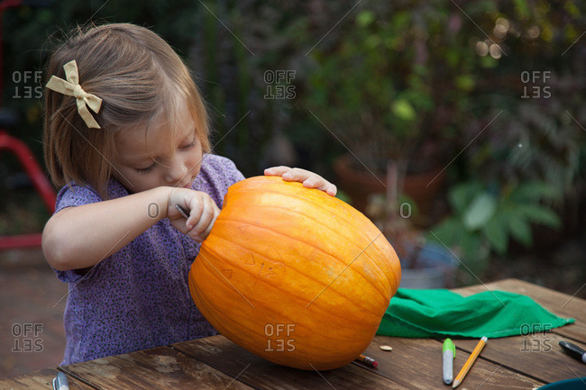 Girl scooping out the inside of a carved pumpkin