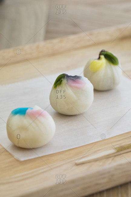 Three colorful dumplings served on a wooden board