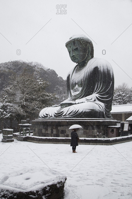 Person standing under an umbrella beneath large statue of the Buddha on a snowy day