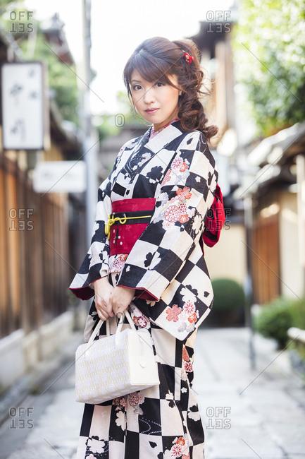 Fashionable young Japanese woman wearing modern kimono and holding purse