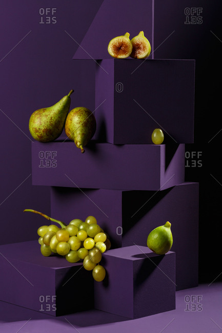 Pears, figs and grapes on purple geometrical shapes
