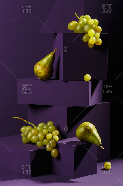 Pears and grapes on purple geometrical shapes