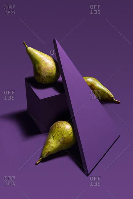 Pears between purple geometric shapes