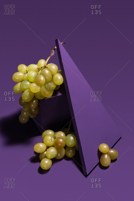 Grapes between purple geometric shapes