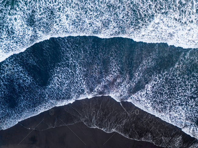 Waves coming in from the sea on black sand beach in Bali, Indonesia
