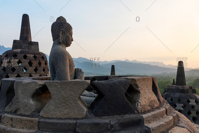 A Buddha statue in a Buddhist complex in Java at sunset, Indonesia.