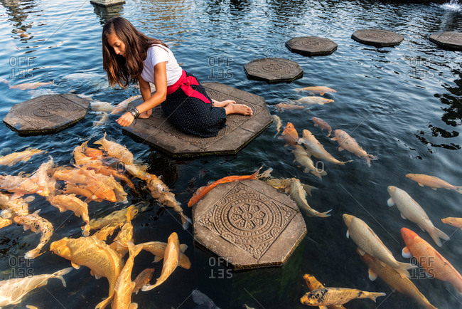 Woman feeding koi fishes in Water Palace in Bali, Indonesia