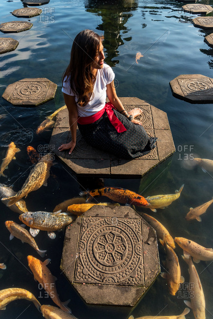 Woman surrounding by koi fishes in Water Palace in Bali, Indonesia