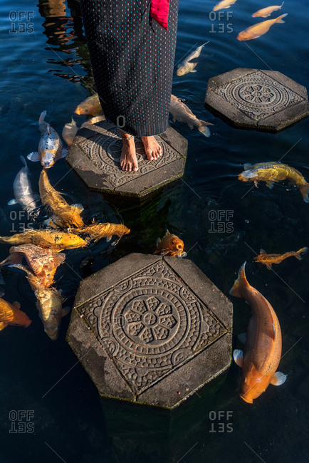 View Of Feet And Koi Fish in a water temple in Bali, Indonesia