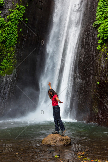 Woman in front of a waterfall in Bali, Indonesia
