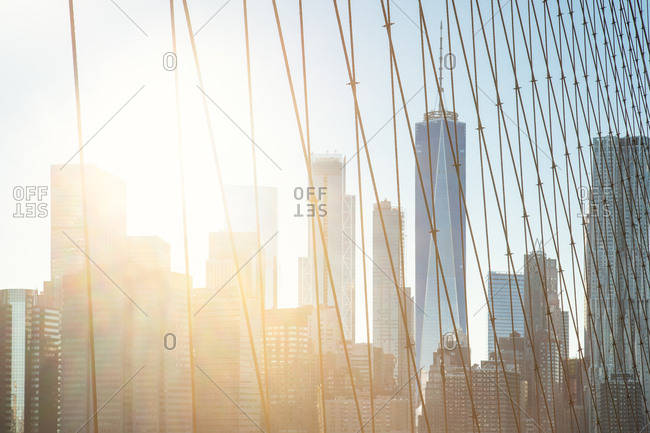 View of city skyline through cables on bridge