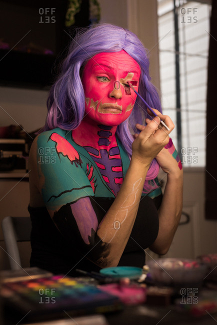Woman painting her face with brush for Halloween celebration