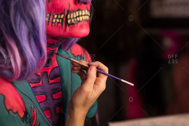 Woman painting her body for Halloween celebration