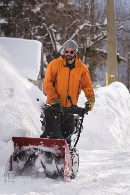 Man using snow blower machine in snowy region during winter