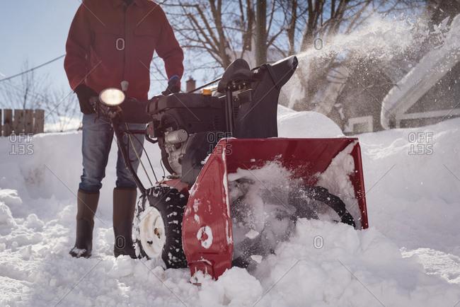 Man using snow blower machine in snowy region during winter