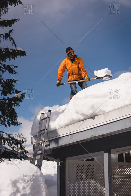 Man cleaning snow from roof top of his shop during winter