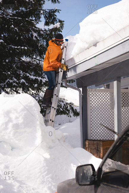 Man climbing on a ladder to clean snow from roof top of his shop during winter