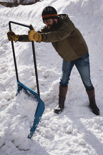 Man cleaning snow with snow pusher during winter