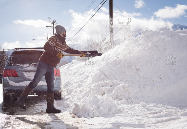 Man cleaning snow with snow shovel during winter