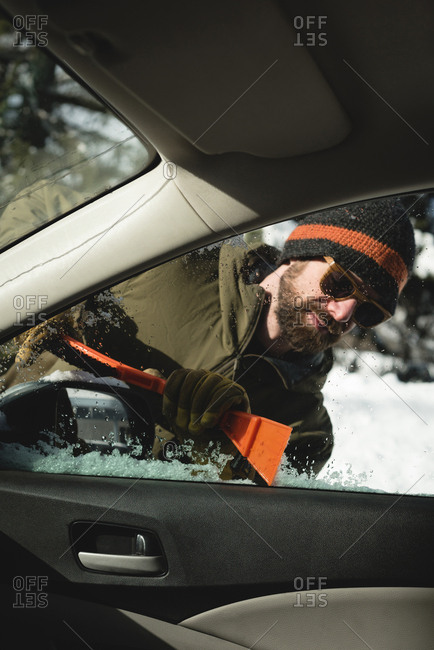 Man cleaning snow from car windshield during winter