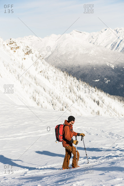 Male skier walking on a snowy mountain during winter