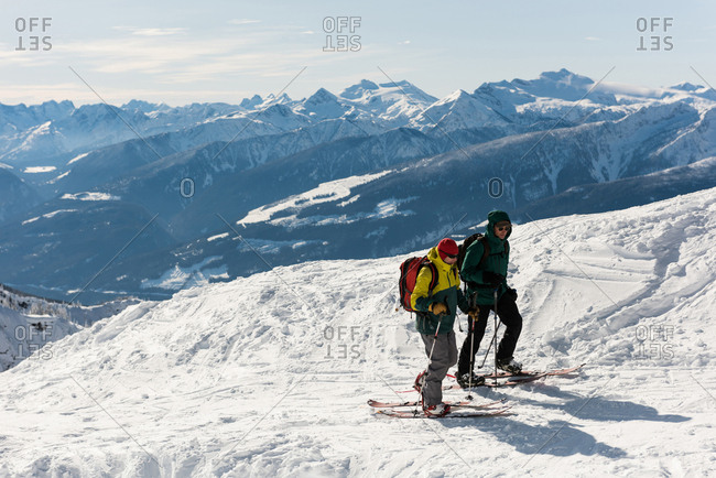 Male and female skiers walking on a snowy mountain during winter