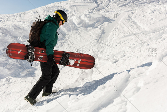 Skier walking with ski board on a snowy mountain during winter