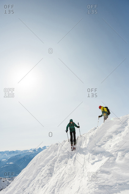 Male and female skiers skiing on a snowy mountain during winter