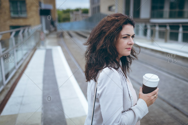 Young businesswoman with coffee cup standing at railway station