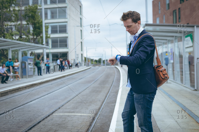 Businessman checking time in his smartwatch at railway station