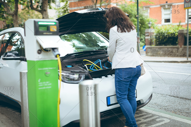 Rear view of businesswoman charging electric car at charging station