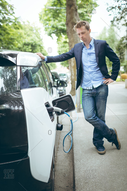Young businessman charging electric car at charging station