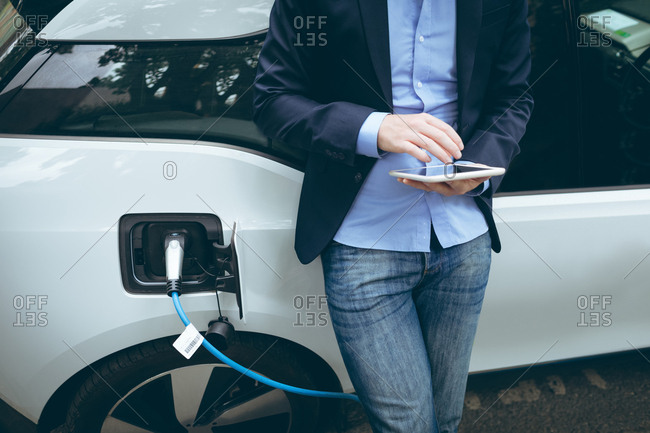 Businessman using digital tablet while charging electric car at charging station