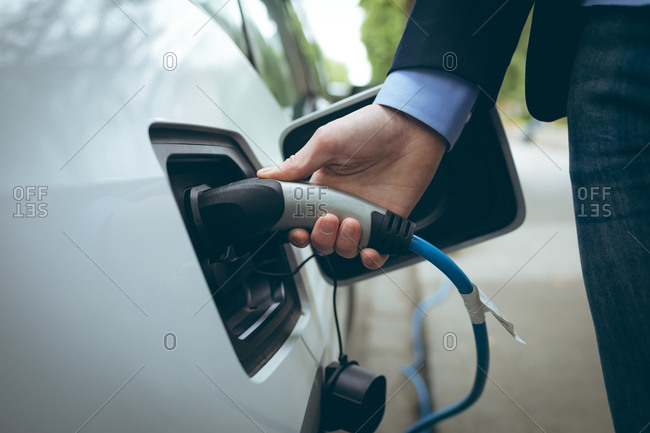 Close-up of businessman charging electric car at charging station