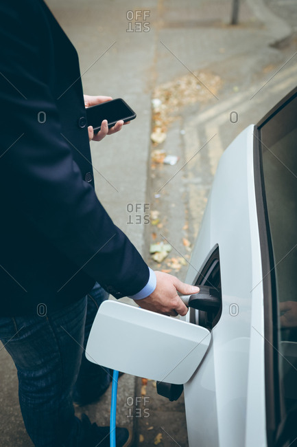 High angle view of businessman using mobile phone while charging electric car at charging station