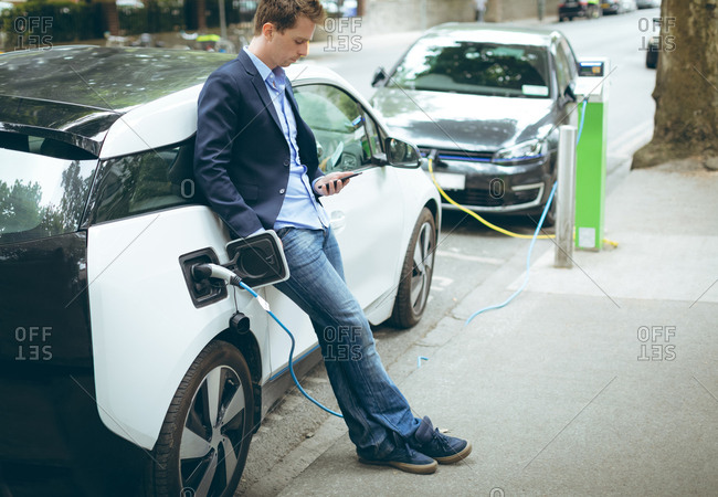 Businessman using mobile phone while charging electric car at charging station