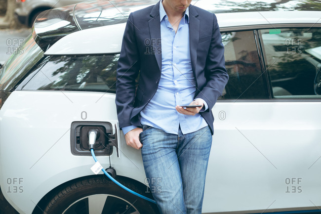 Mid section of businessman using mobile phone while charging electric car at charging station