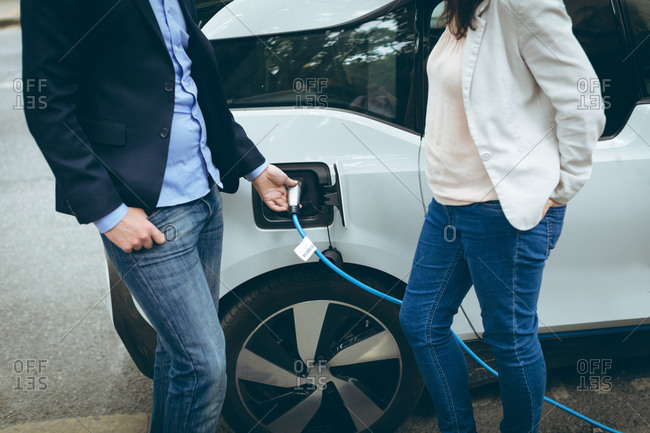 Mid section of business colleagues charging electric car at charging station