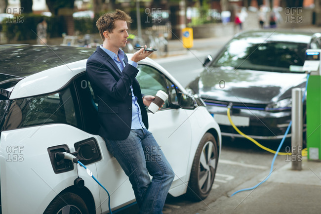 Businessman talking on mobile phone while charging electric car at charging station