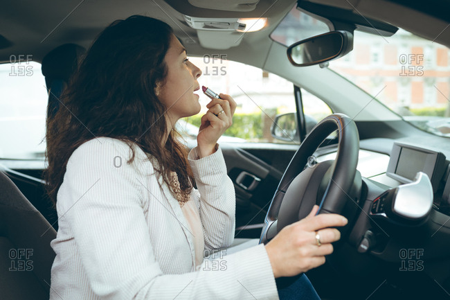 Side view of businesswoman applying lipstick in car